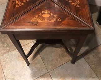 This is an antique handkerchief game table with marquetry.  On consignment.