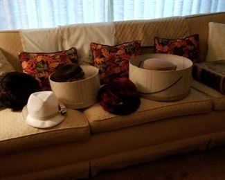 a nice long davenport. many newer hats. an antique family-type bible and leather bound books.