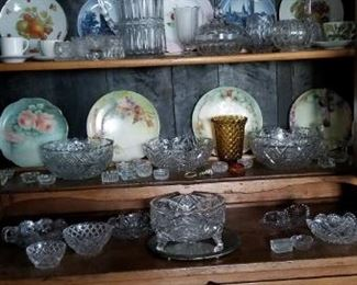 nice oak china cabinet/hutch with nice pulls. two piece. crystal champagnes and wine glasses. hand painted dishes. eapg water pitcher, spooner, butter dome and rose bowl. lots of salt cellars and clear-cut glass. nice mirrored plateau.