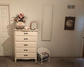 Child's wicker rocker and white dresser.