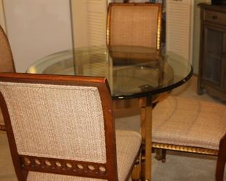 Glass and brass dining table with four chairs.