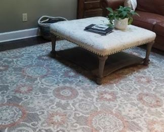 Fabric ottoman and neutral rug