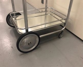 vintage tubular chrome + glass italian bar cart on wheels; mirrored bottom shelf.