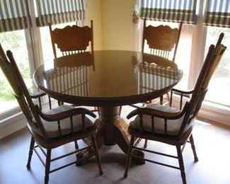 Oak round table with 4 pressed back chairs and glass cover for the top