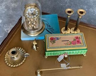 lot of items on table top including brass, clock