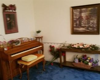 piano, behind the sofa table , flowers and more picture has been sold