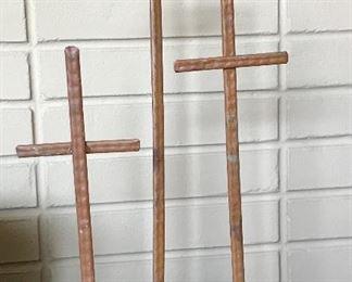 Folk art metal crosses with stone bases.
