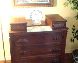 Victorian walnut chest of drawers with marble insert. and folk art print behind.