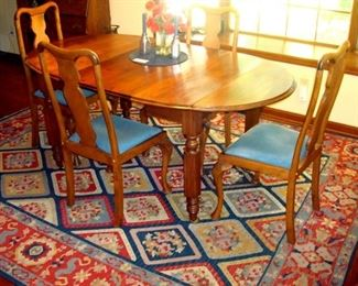 Victorian drop leaf extension table with four Queen Anne chairs and room size vintage rug.