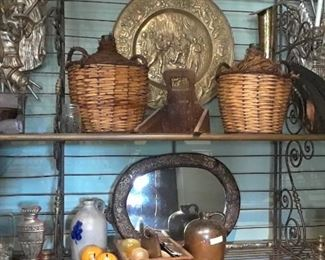 Large French baker's rack boasts French demi-johns, Mexican pottery and interesting art accessories.