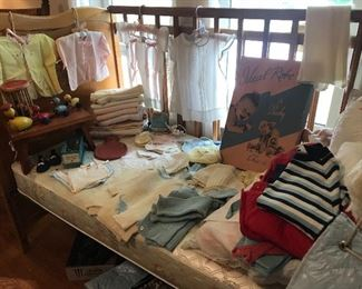 Antique baby clothes, antique breast pump, antique baby shoes and vintage toys