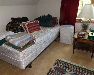 Twin bed; bedding; throw rugs; end table; throw pillows