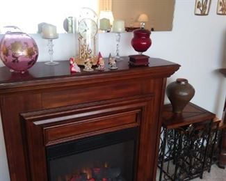 Vintage cranberry glass vases, Electric fireplace, End tables.