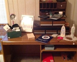 Computer desk, storage drawers, wooden unit with cubbies and two drawers, conair lighted mirror, desk lamp, Nono hair removal system, AT&T and Norte phones, doily, rosaries and Blessed Mother statues