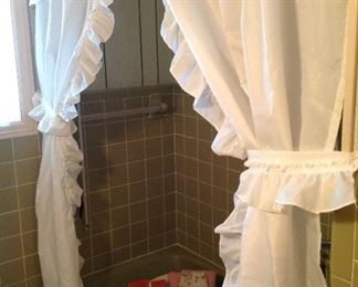 Pretty white shower curtain, basket full of towels