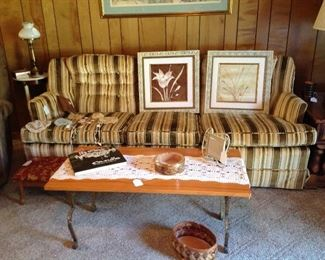 Couch, pair of framed prints, collection of old baby bonnets,  coffee table - iron base with wooden top, Rodriquez book, decorative ashtray, picture frame, basket