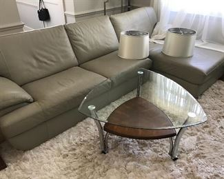 Leather sectional and glass table on shag carpeting