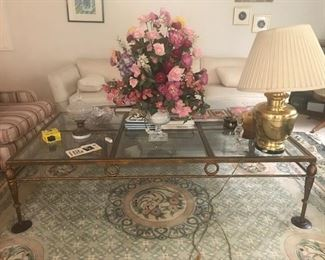 Rug, glass coffee table, white couch, brass lamps
