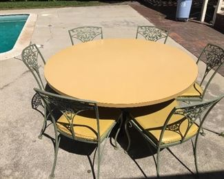 Laminate kitchen table. 4.5 foot diameter, metal base. 6 metal chairs with cushions.