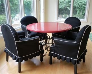 Iron base wooden round red painted top dining table with four slip covered armchairs