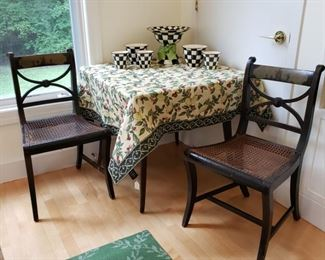 Two of three Hitchcock chairs and a black painted square table under the table cloth