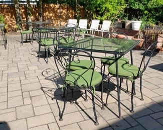 Three metal and glass top square patio tables each photographed with a set of four chairs