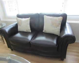 WE HAVE 2 OF THESE CHOCOLATE BROWN LEATHER NAIL HEAD LOVE SEATS. PERFECT CONDITION!