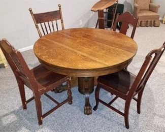 Antique round wood table with leaf. Assorted antique chairs
