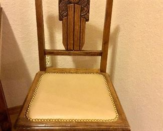 Carved back chair with leather seat and nailhead trim