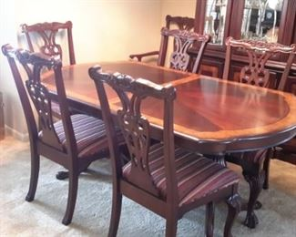 MAHOGANY CHIPPENDALE STYLE DINING TABLE & CHAIRS: Mahogany top table with banded edge, double pedestal base with splayed carved legs. 6 Chippendale 2 armed and 4side chairs with carved and openwork back,front feet ending in claw and ball feet, striped floral upholstery, stunning matching dining room!