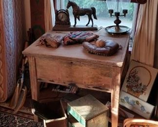 Old desk with hurricane lamp, netal horse, and old baseball gloves.