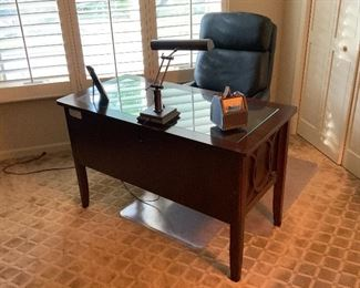 24 inch x 48 inch office desk with glass top insert, cherry finish and black leather office chair and lamp