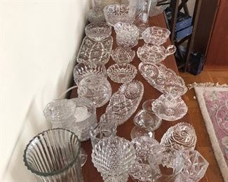 Collection of vintage glass services pieces, glass ice bucket with glass coaster, and vintage vases.