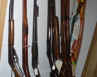 DAISY BB GUNS INCLUDING THE FAMOUS CHICAGO WOODEN - 2ND FROM LEFT, MORE DAISY GUNS IN THE TWO BOXES, 2 JAPANESE RIFLES AND WINCHESTERS.  LOOK AT JAPANESE BAYONET AND DAISY SCOPE NEXT PICTURES