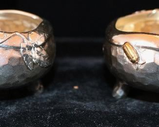 A rare pair of Tiffany antique sterling  and mixed metal hammered Japanese style salt cellars with spot hammered surfaces and applied copper details.