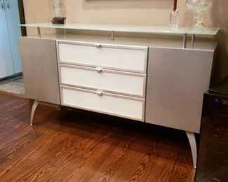 Contemporary sideboard with three drawers flanked by two doors with an elevated glass top