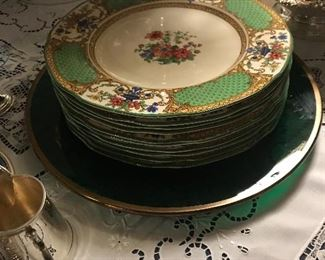 A set of antique service plates sitting on a large glass hunter green charger.