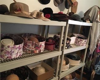 Hats of many shapes and sizes, original hat boxes, and wooden hat stands.