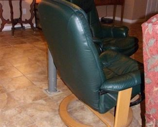Mid Century Modern leather swivel chairs with ottomans.