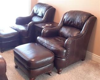 Two Flexsteel leather armchairs with nailhead trim and ottomans.