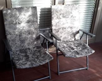 Two very clean foldable lawn chairs.