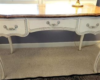 Natural wood finish atop french provincial lady's desk