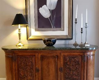 Print, lamp, bowl & candle holders atop carved credenza