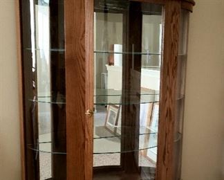 Oak lighted curved glass china cabinet has claw feet