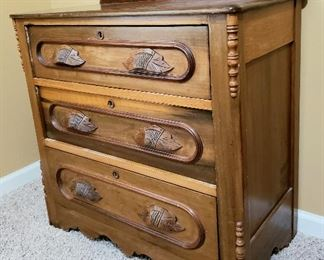 Three drawer antique chest has carved pulls