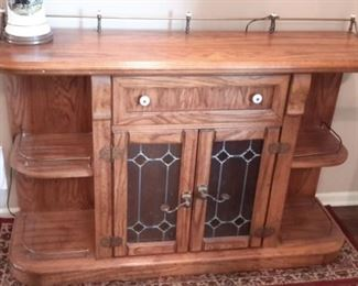 Oak entry/sofa table with lead design glass doors and rail accent