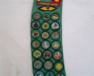 Girl Scout sash with badges, pins.
