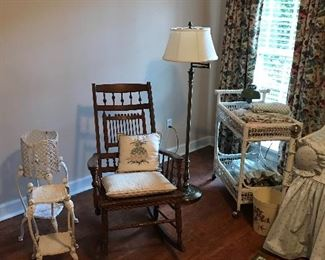 Antique rocker, cast iron plant stands, and wicker cart