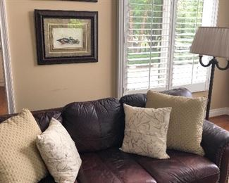 Leather couch, floor lamp and framed prints