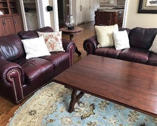 Leather couch and love seat, large coffee table and round area rug, and side table with iron hurricane candle holder